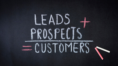 Leads, prospects, customers formula chalk drawing on dark background.